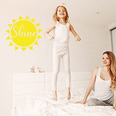 young and beautiful blonde mom playing in bed with her little cute daughter at home in the bedroom